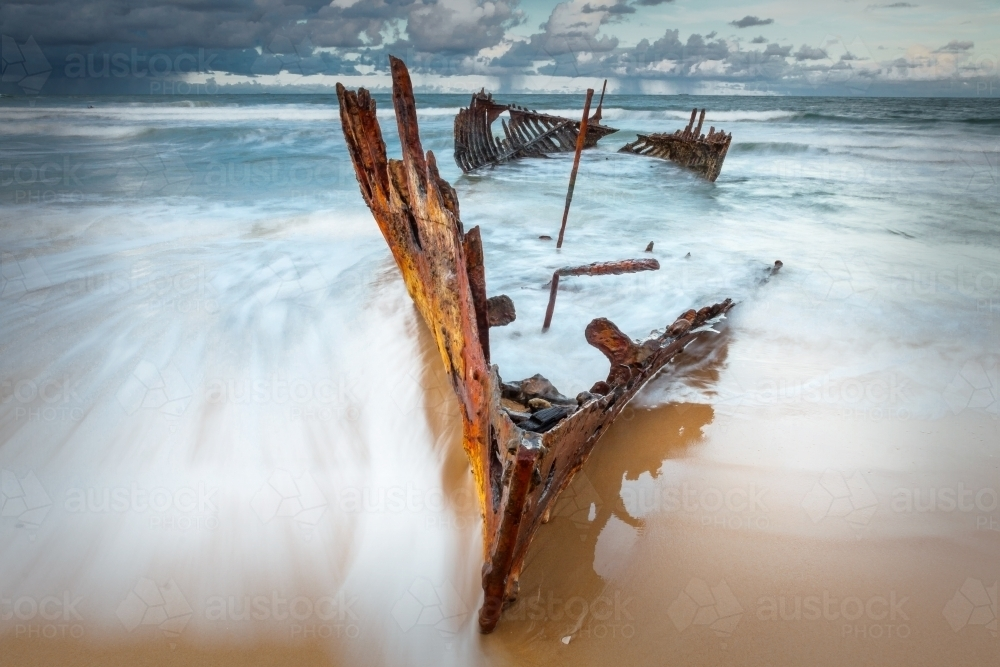 Waves engulfing the bow of a shipwreck on a beach - Australian Stock Image