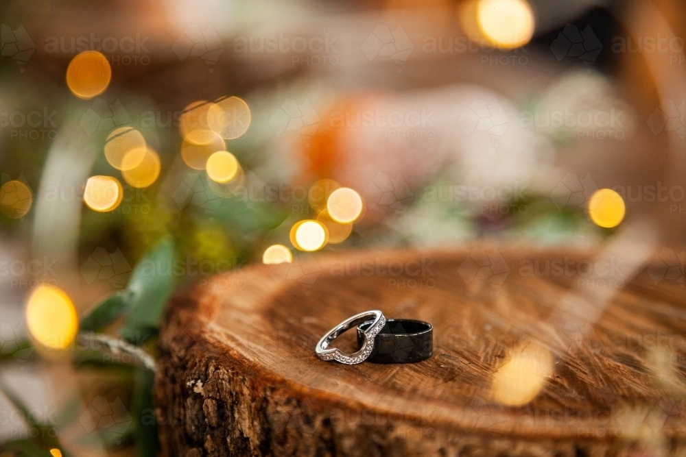 Wedding bands for marriage ceremony on wood round with bokeh lights - Australian Stock Image