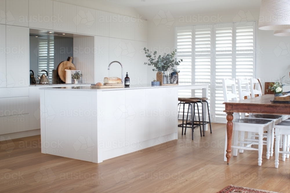White kitchen with dining table, wooden floor and shutters - Australian Stock Image