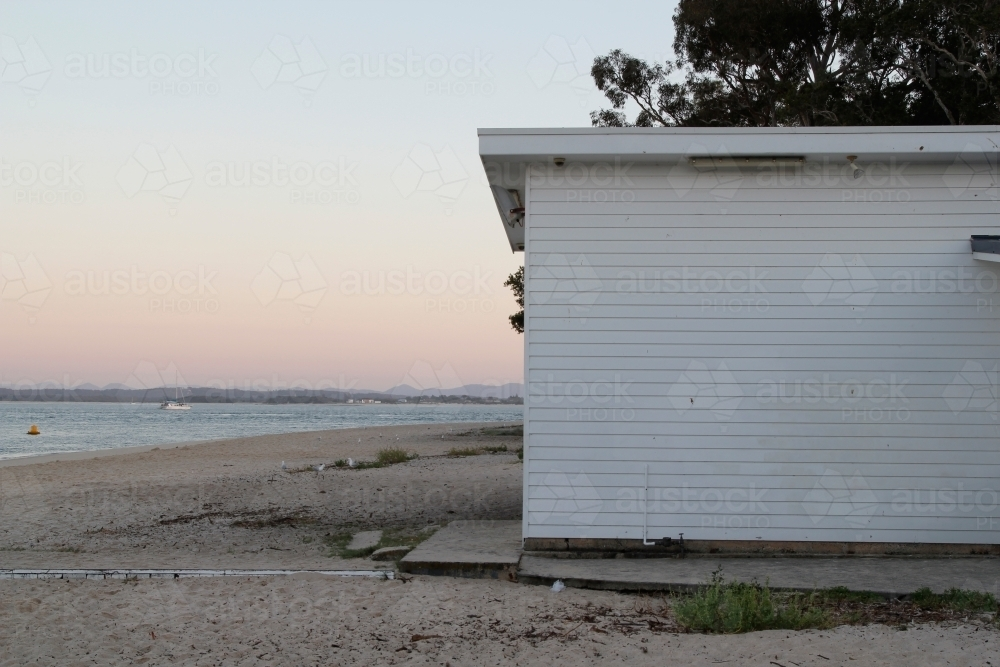 White weatherboard building on the beach at sunset - Australian Stock Image