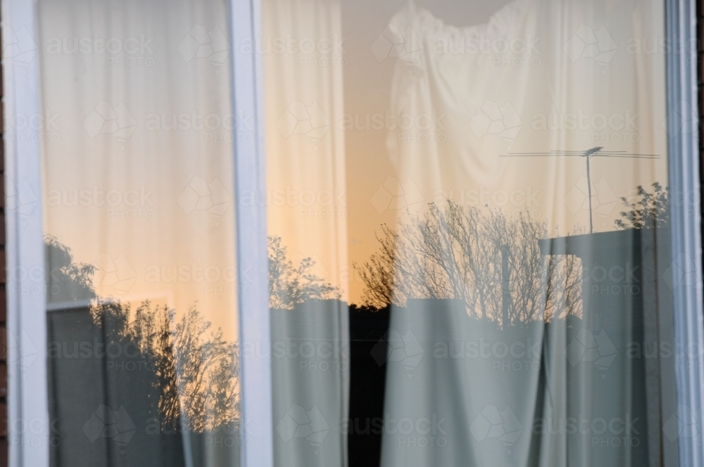 Window reflection of houses and trees at sunset during winter - Australian Stock Image
