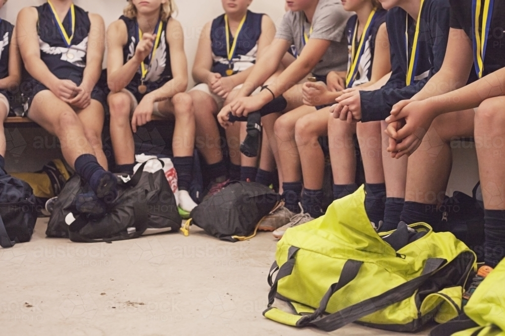 Winning football team players debrief in locker room - Australian Stock Image