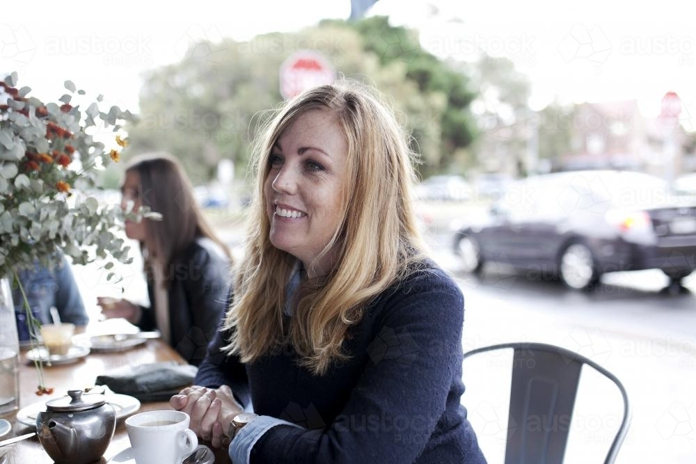 Woman at cafe smiling and looking to the side - Australian Stock Image