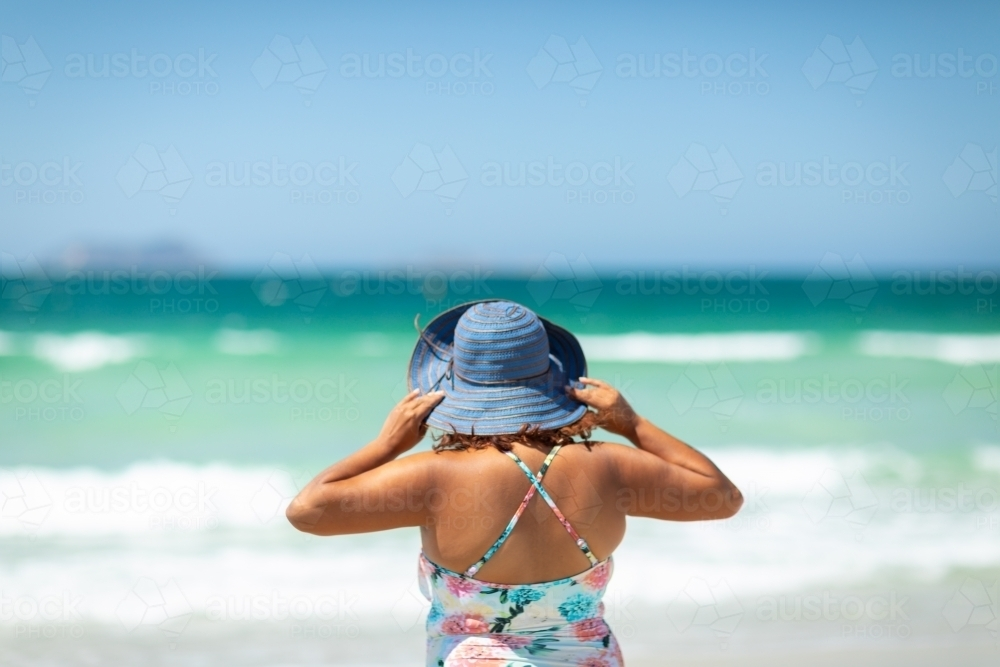Woman at seaside holding hat on head from behind - Australian Stock Image