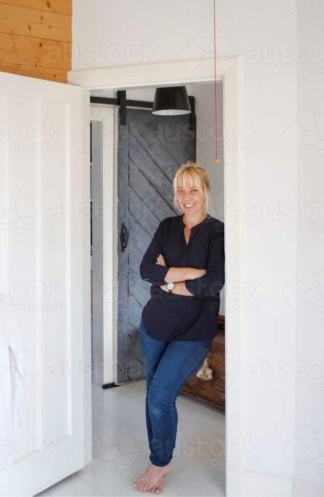 Woman casually leaning against doorway in white walled home - Australian Stock Image