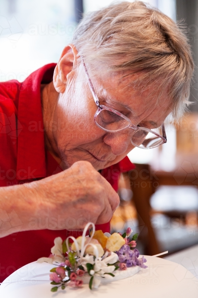 Woman Decorating Birthday Cake With Hand Made Native Flower Topper