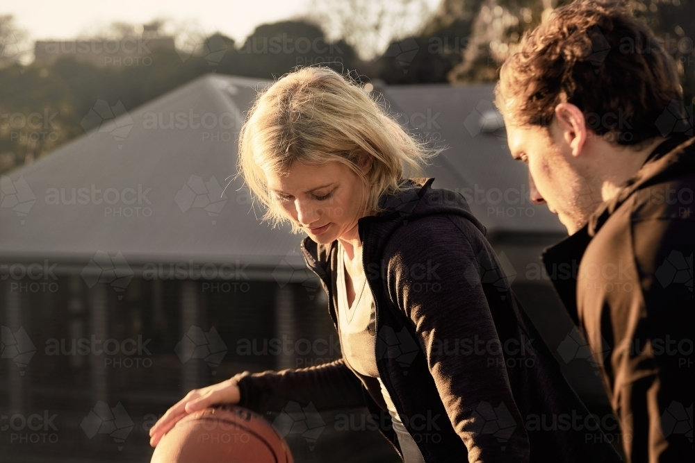 Woman dribbling basketball in one on one game - Australian Stock Image