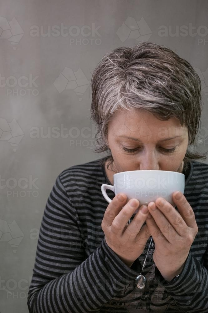 Woman drinking first coffee of the day - Australian Stock Image