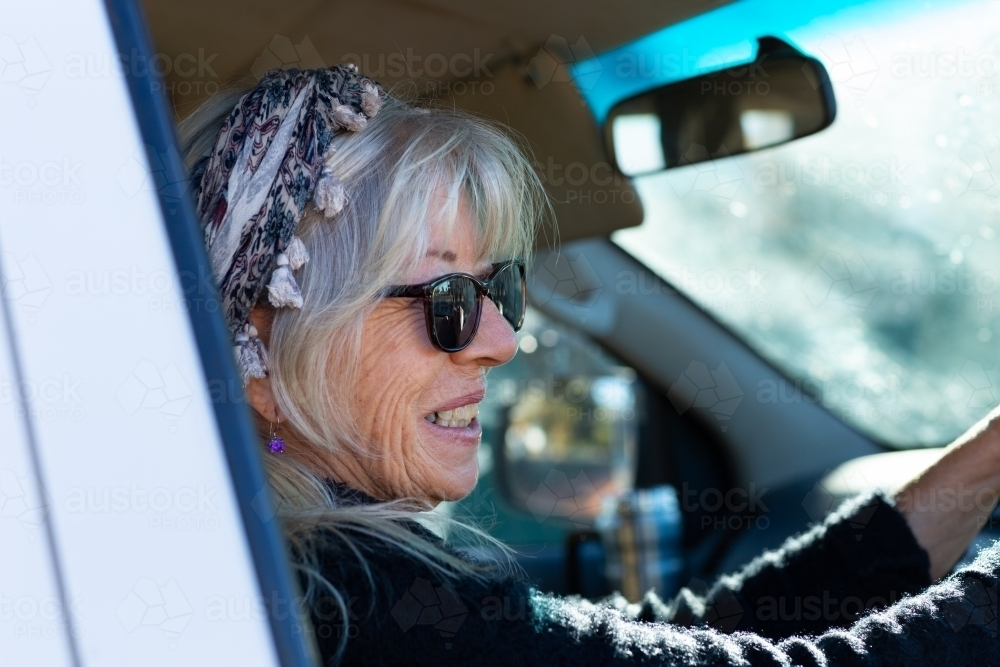 woman driving a vehicle seen through car window - Australian Stock Image