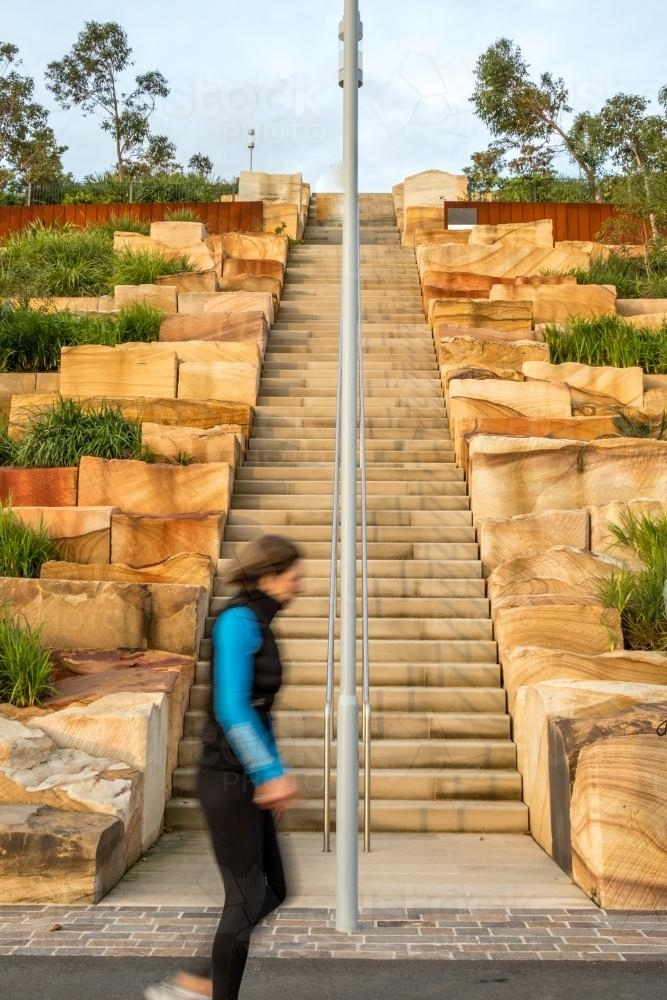 Woman exercising walking past Sandstone stairs at Barangaroo - Australian Stock Image
