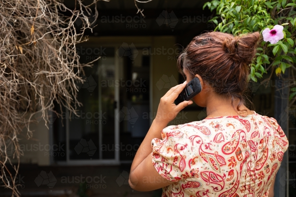 woman from behind holding flip phone to ear - Australian Stock Image