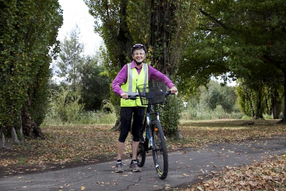 Woman in high visability vest standing with bike - Australian Stock Image