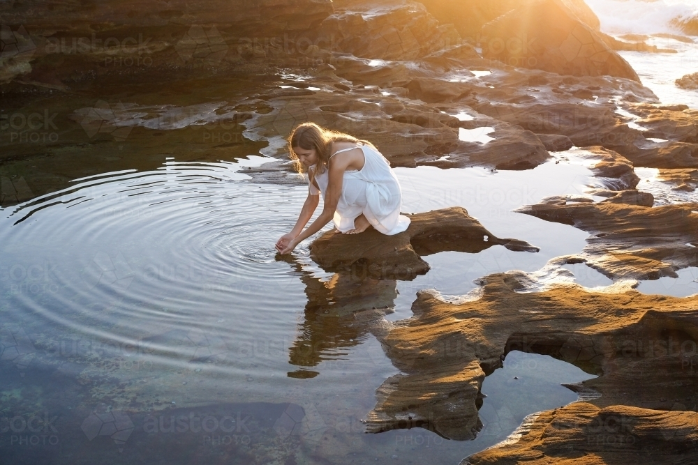 Woman kneeling beside rockpool with golden light and ripples - Australian Stock Image