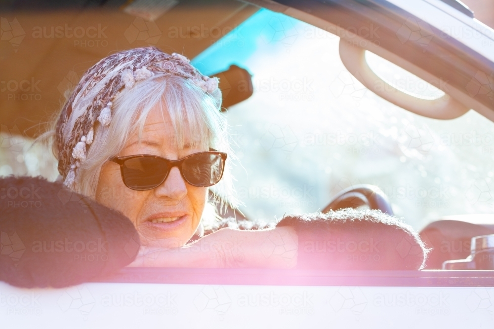 woman looking out car window backlit with sun flare - Australian Stock Image