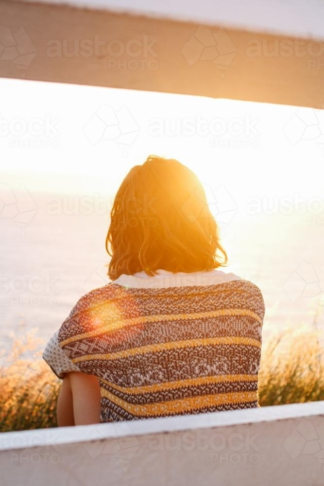 Woman looking out to sea bathing in the morning light - Australian Stock Image