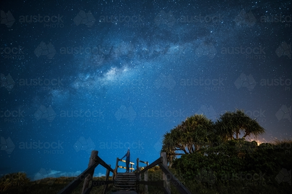 Woman looking up pointing to the Milky Way above her in the sky. - Australian Stock Image