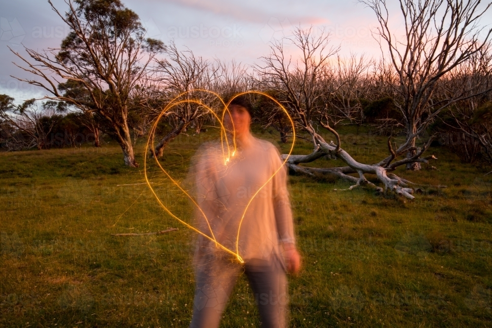 Woman making a heart shape with a sparkler at dusk - Australian Stock Image