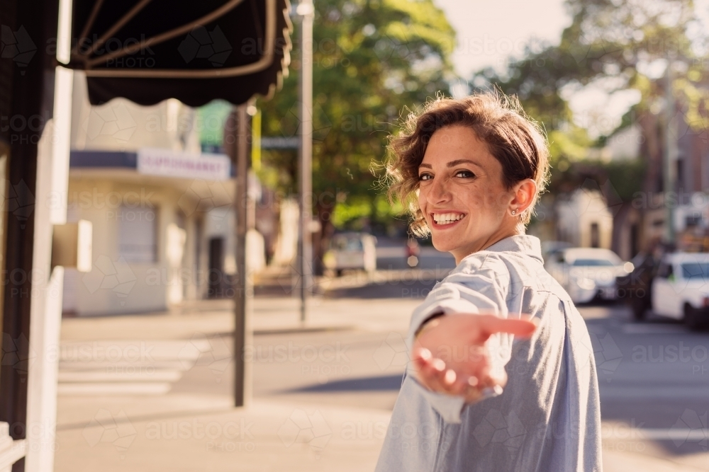 woman reaching back with hand out - Australian Stock Image