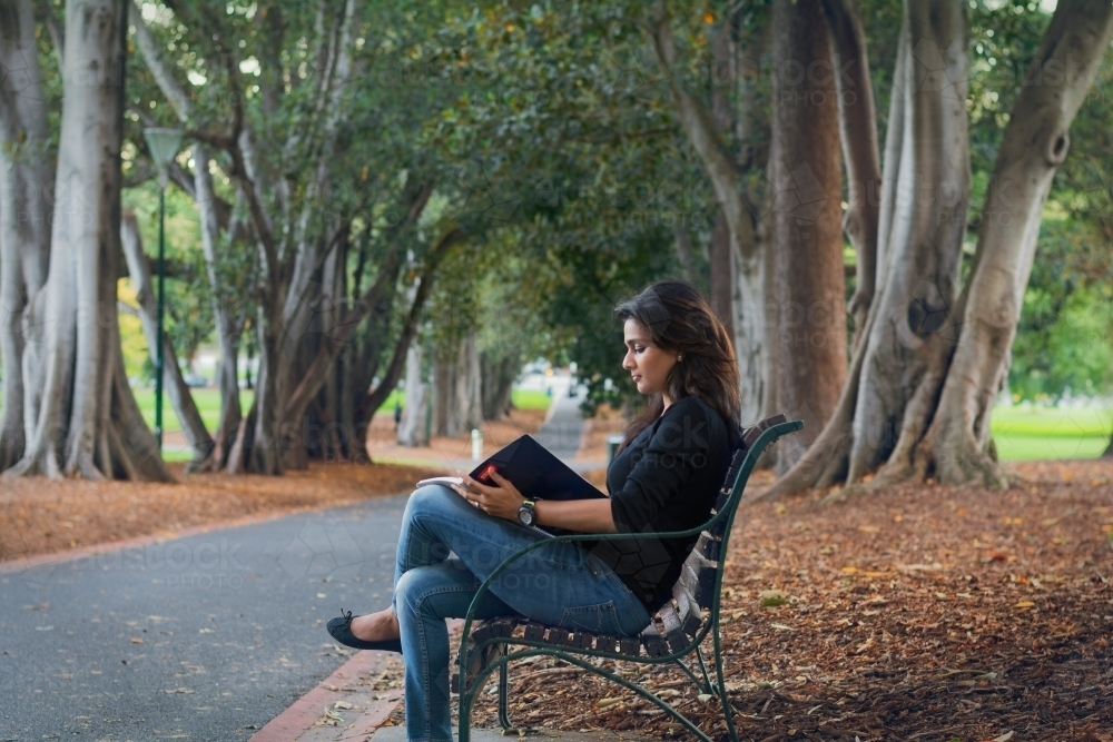 Woman reading a book on a park bench - Australian Stock Image