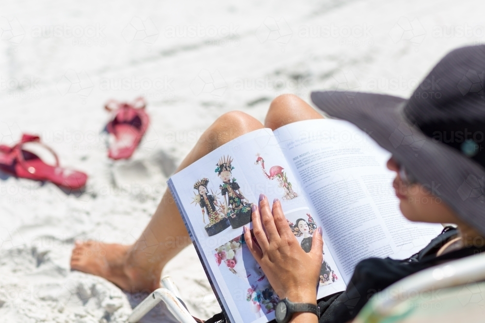 Woman relaxing and reading magazine on white sand beach - Australian Stock Image