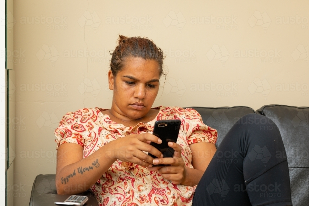 woman relaxing on sofa scrolling on smartphone - Australian Stock Image