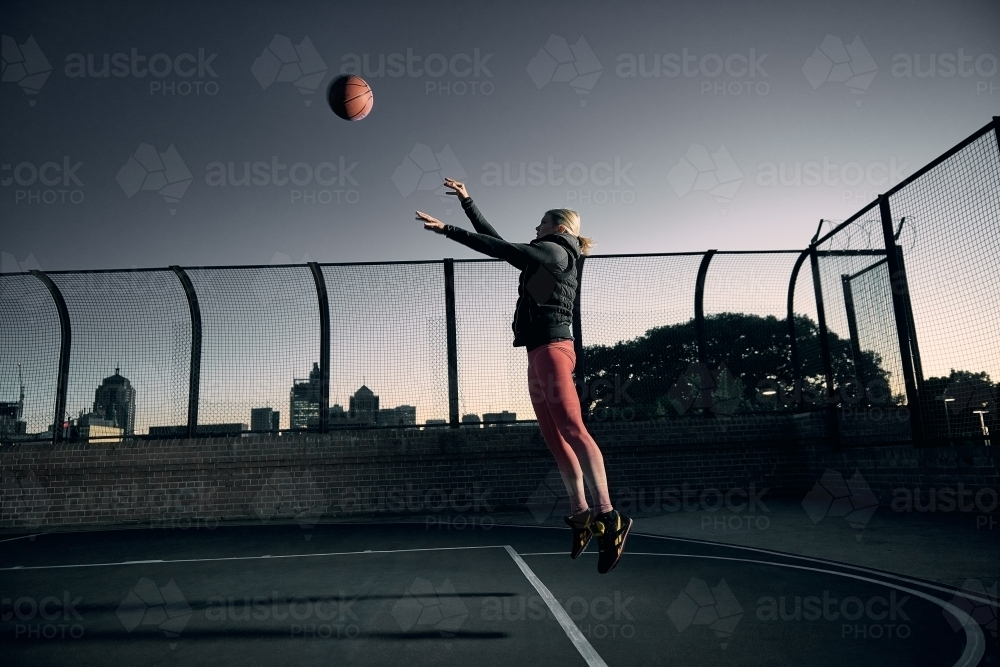 Woman Shooting basketball on court - Australian Stock Image