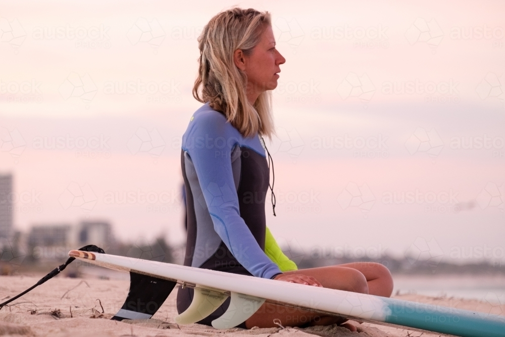 Woman sitting on beach next to surfboard wearing wetsuit looking out to sea at sunrise - Australian Stock Image