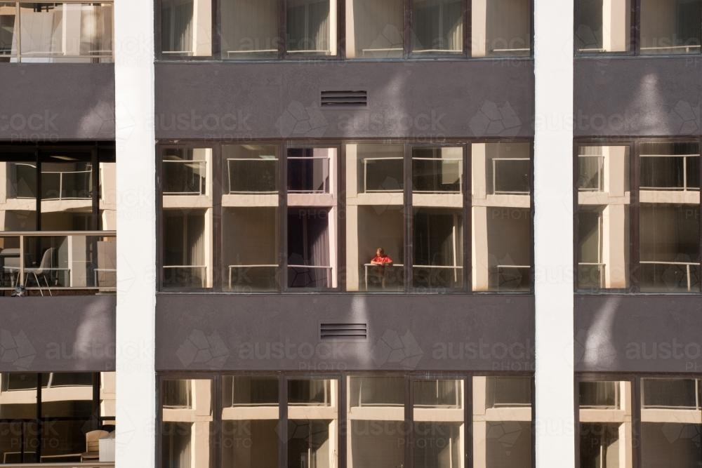 Woman standing on the balcony of a high rise apartment - Australian Stock Image