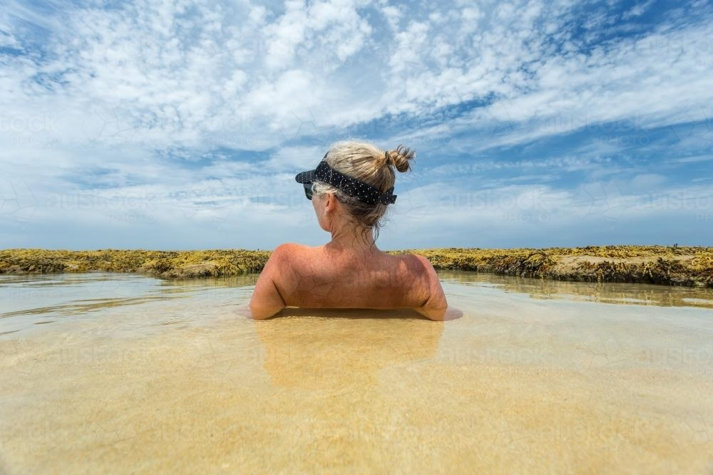 Woman sunbathing in shallow water - Australian Stock Image