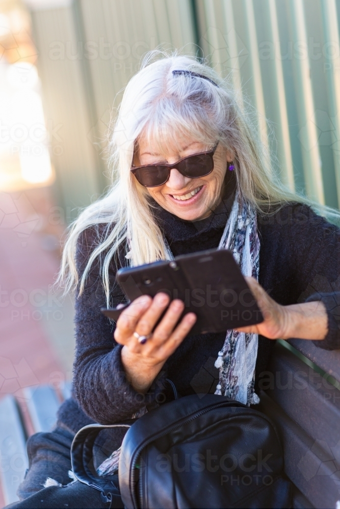 Woman wearing sunglasses looking at smartphone - Australian Stock Image
