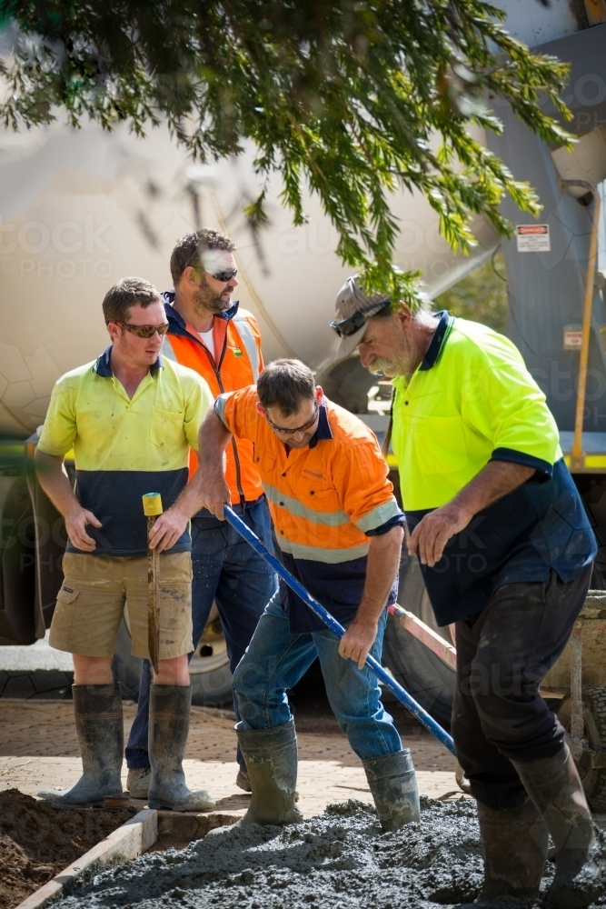 Workers in hi-vis laying concrete - Australian Stock Image