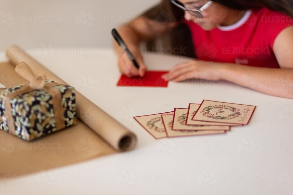 wrapping paper and cards in foreground with girl writing on envelope - Australian Stock Image