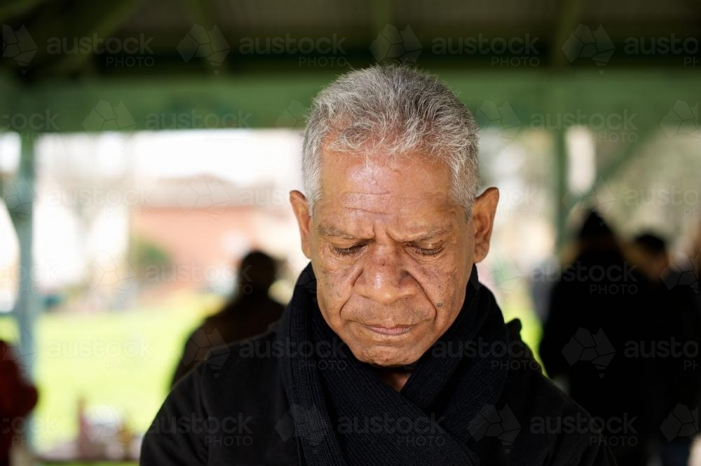 Wurundjeri Elder in Shelter Looking Down with Sad Expression - Australian Stock Image
