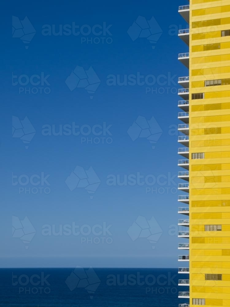 Yellow apartment building with blue sky and sea - Australian Stock Image