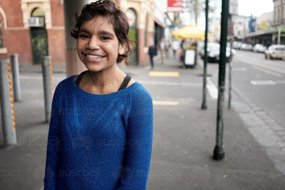 Young Aboriginal Woman in town street - Australian Stock Image