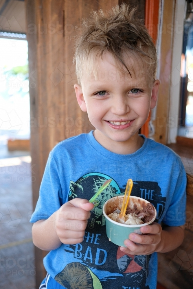 Young blonde boy eating ice cream in a suburban gelateria in Brisbane - Australian Stock Image
