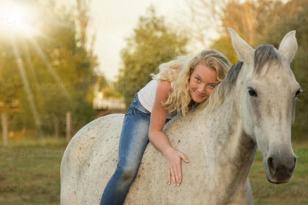 Young Blonde Girl Lying On Her Horse