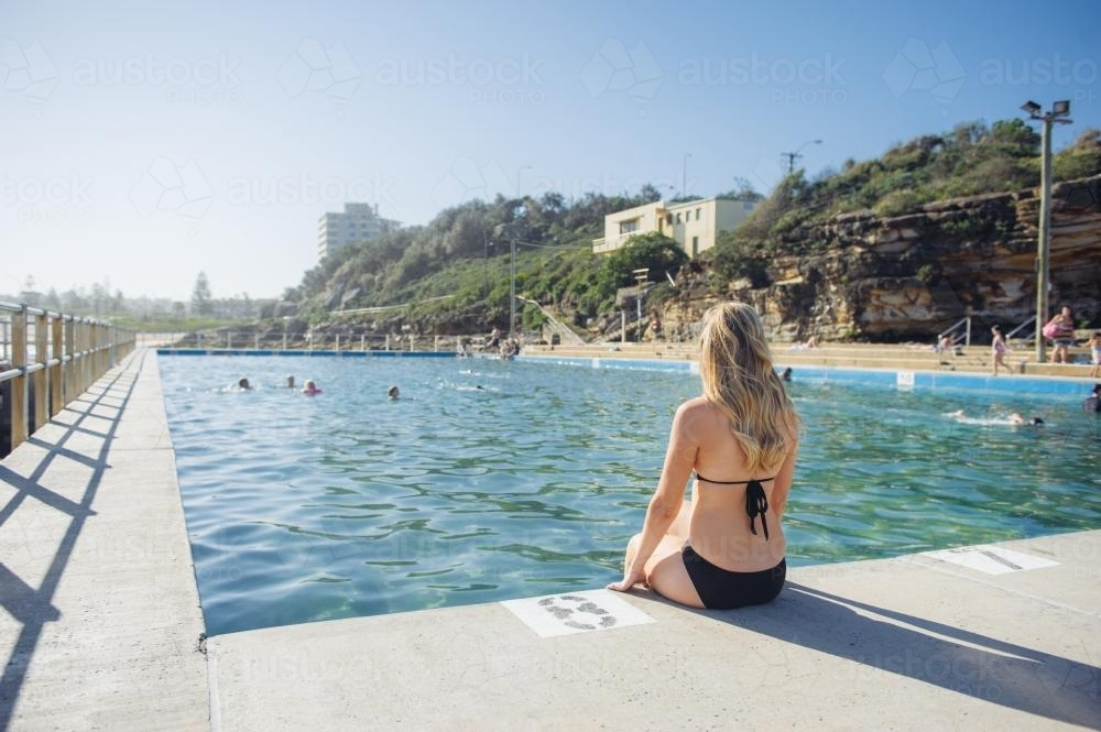 Young blonde Woman sitting on the side of an ocean pool - Australian Stock Image