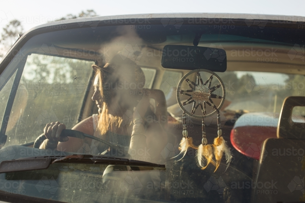 Young bohemian woman driving car into the sunlight - Australian Stock Image