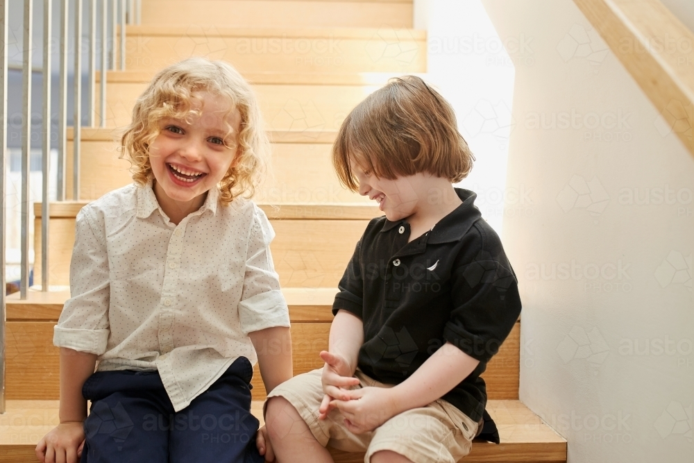 Young boy and girl sitting on stairs - Australian Stock Image