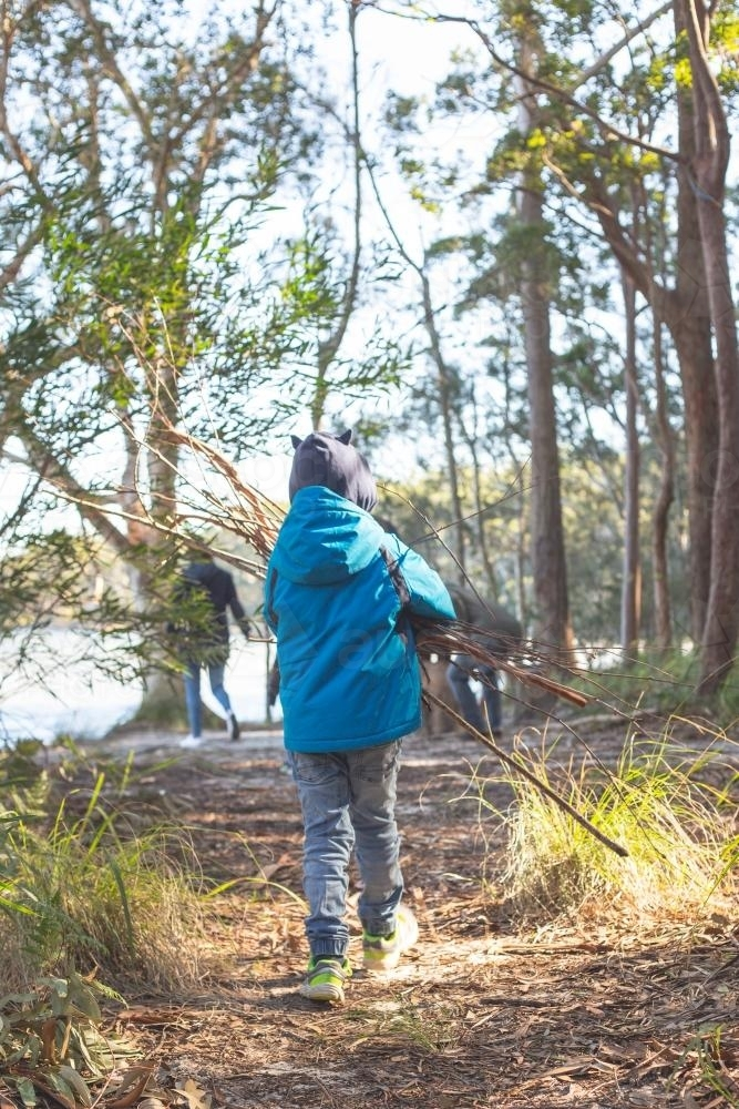 Young boy from behind carrying firewood - Australian Stock Image