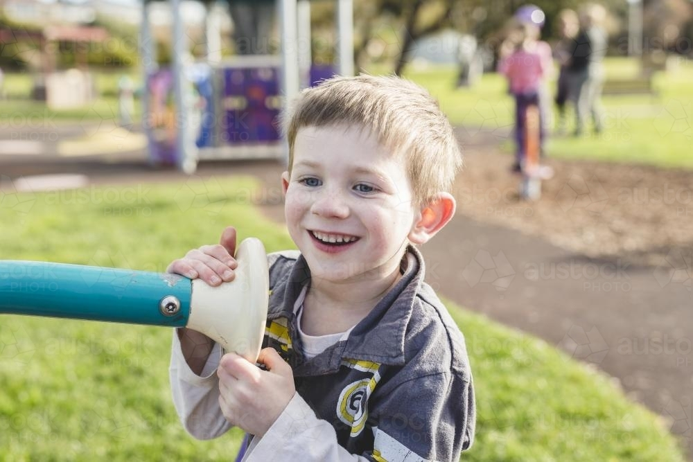 Young boy happily playing at the park - Australian Stock Image