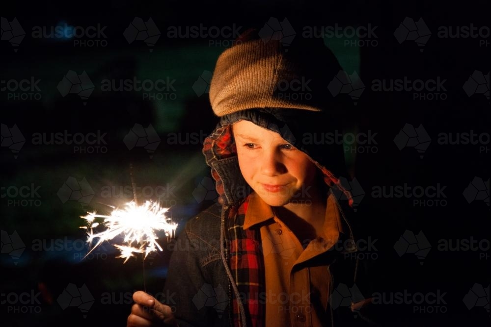 Young boy holding a burning sparkler on a bonfire night - Australian Stock Image