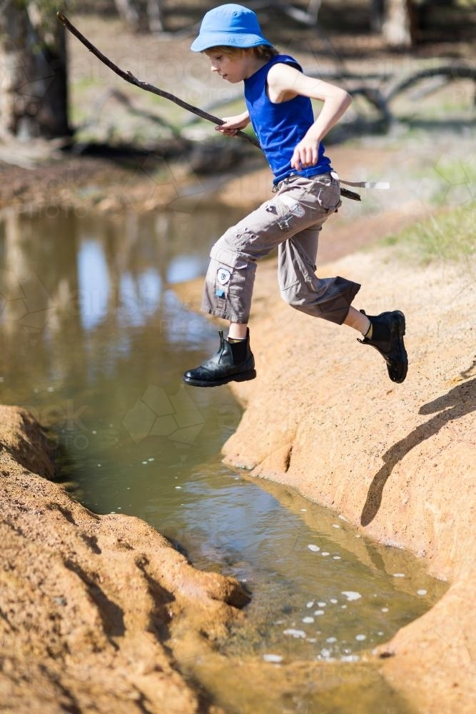 young boy holding a stick while jumping across a creek - Australian Stock Image