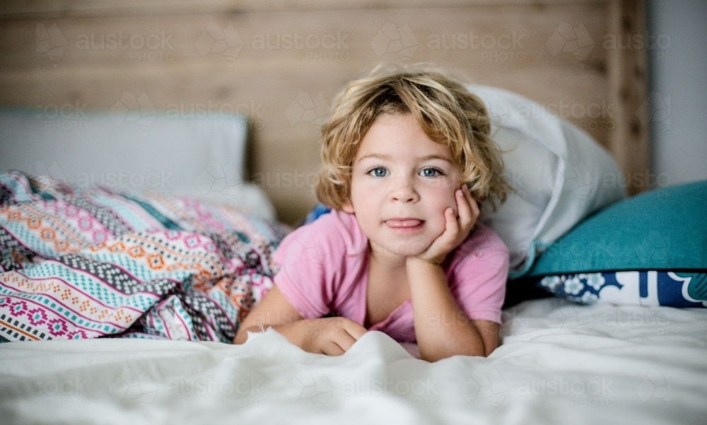 Young boy in bed in natural morning light - Australian Stock Image