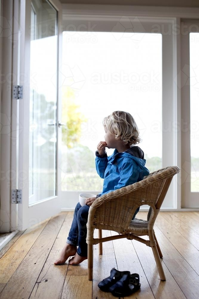 Young boy sitting on chair, eating and looking outside - Australian Stock Image