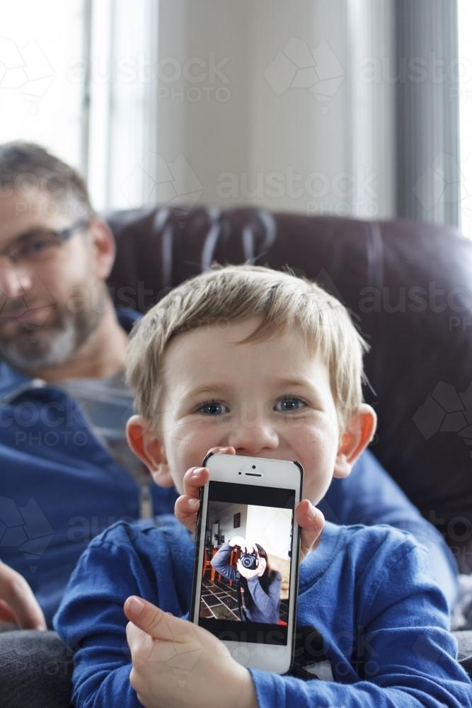 Young boy sitting on fathers lap holding phone with photo on screen - Australian Stock Image