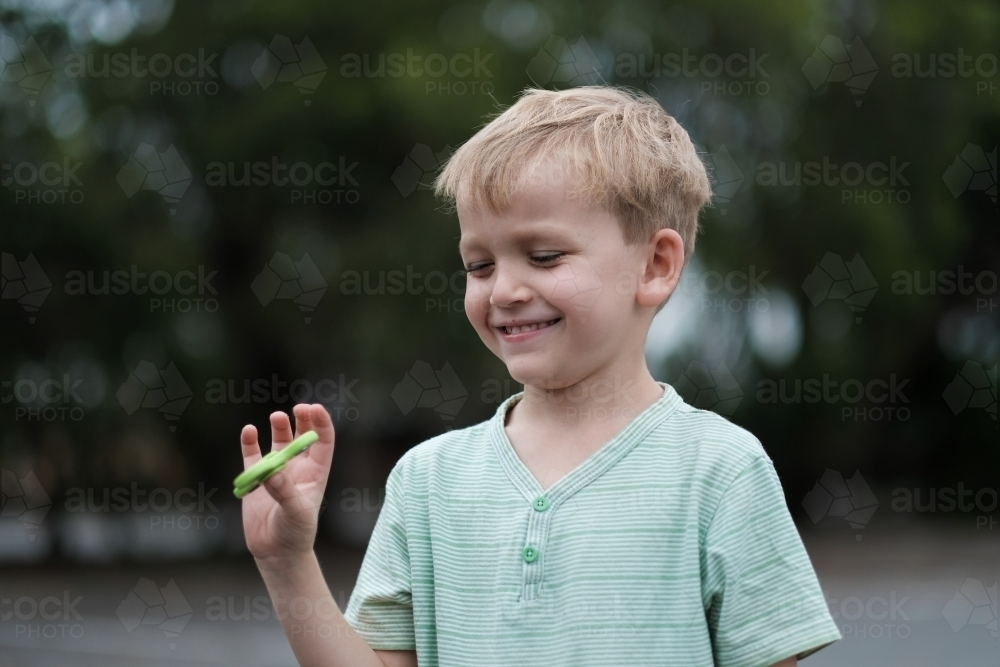 Young boy smiling playing with fidget spinner - Australian Stock Image