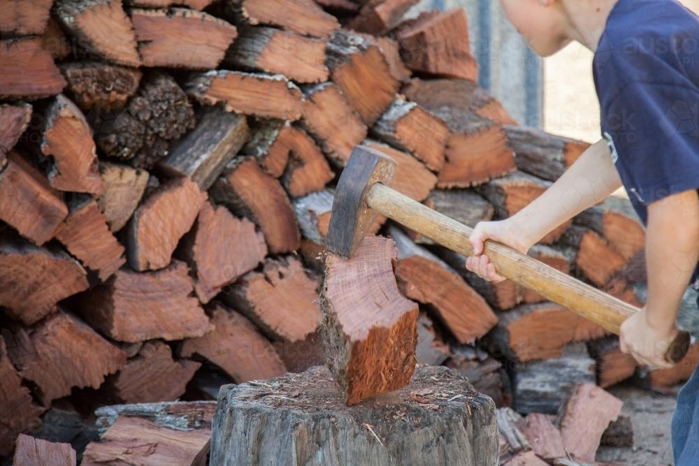 Young boy splitting wood for the fire - Australian Stock Image