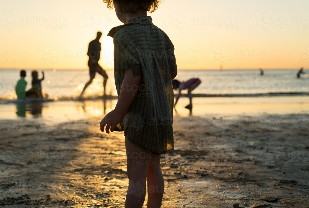 Young boy stands on the beach silhouetted against the sunset - Australian Stock Image